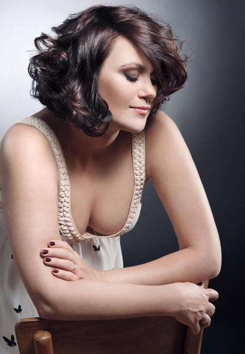 Ravishing short wavy hairstyle cut in long layers and designed with heavy bouncy curls.